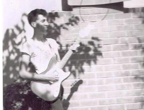 Teenager John plays guitar